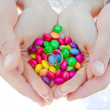 Hands  holding colored candies in which lie wedding rings - Foto Stock