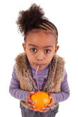 Little black girl drinking orange juice with a straw — Stock Photo