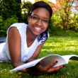 Young Student reading books at the school park - Stockfoto