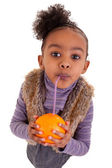 Little black girl drinking orange juice with a straw — 图库照片