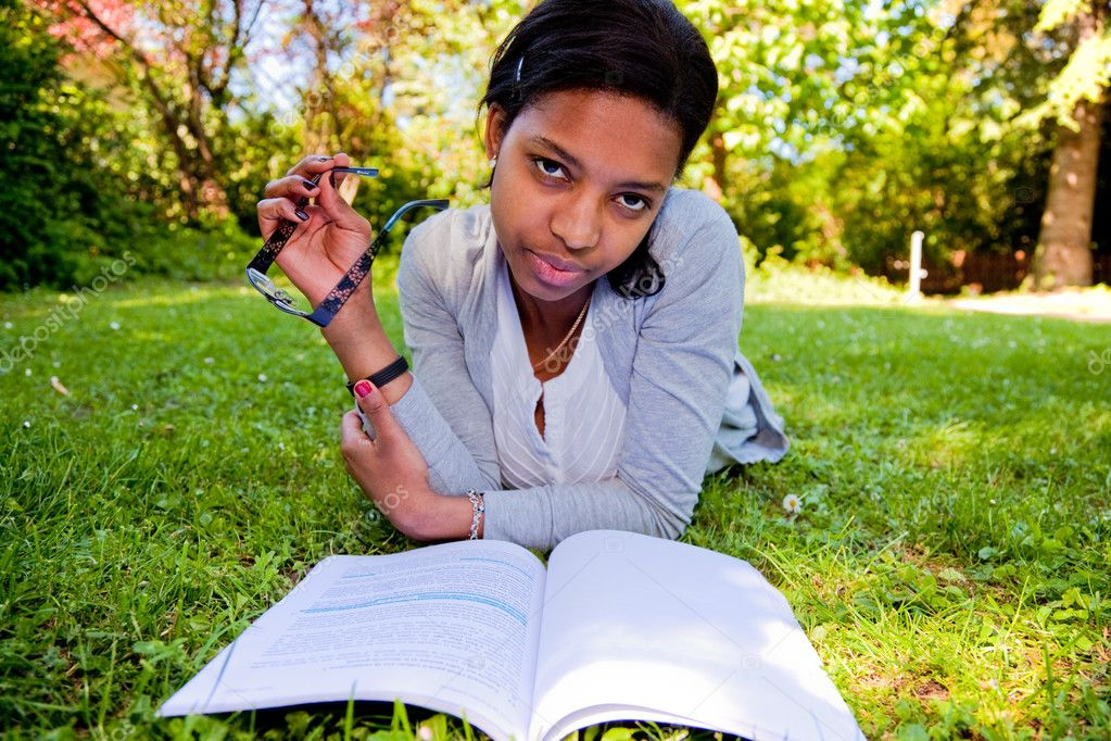 Young Student reading books at the school park  Stock Photo #5141429