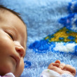 The small beautiful baby lying on a blanket - Stock Photo