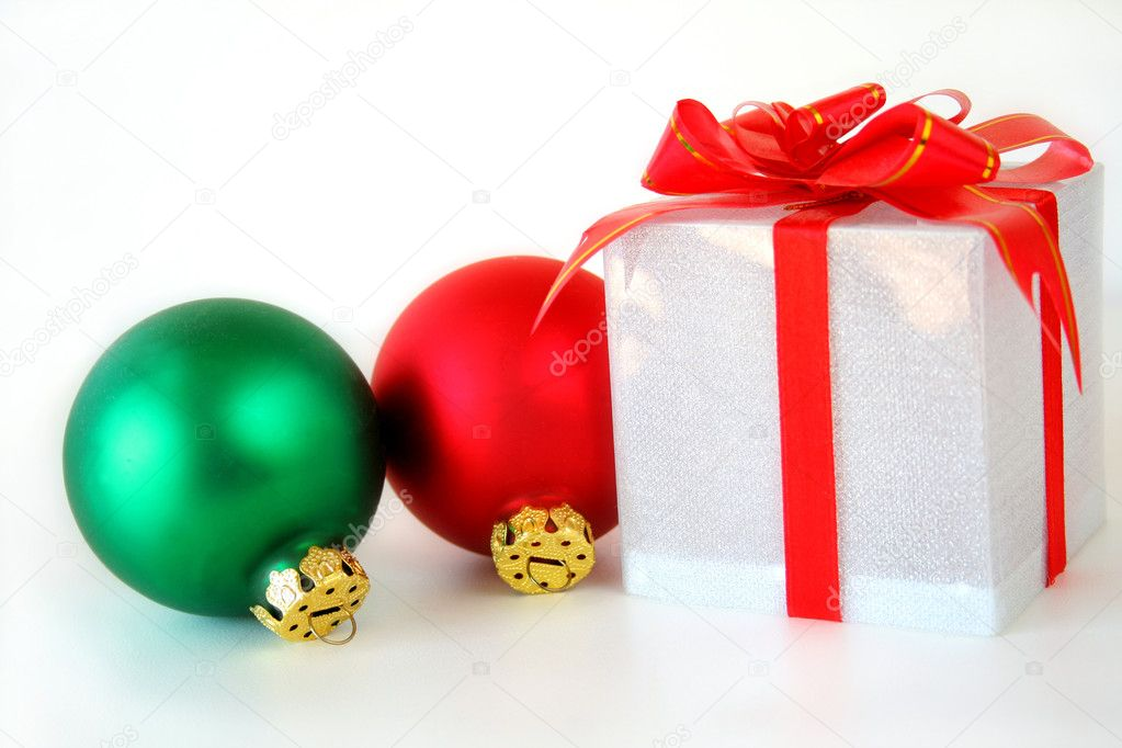 A Christmas gift and ornaments of red and green on a white background. — Stock Photo #5227521