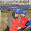 Engineers in a solar panel station - Stock Photo