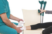 Doctor bandaging ankle — Stock Photo