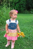 Cute toddler girl with flowers — Stock Photo