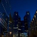 Skyline of modern skyscrapers with illuminated windows and dark sky during — Stock Photo