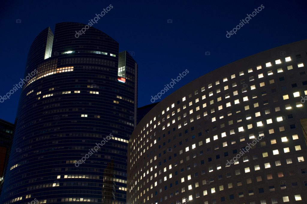 Skyline of modern skyscrapers with illuminated windows and dark sky during the night — Stock Photo #5267958