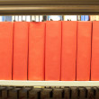 Royalty-Free Stock Photo: Stack of books in red binding on a library shelf