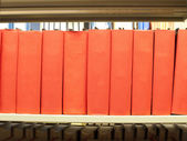Stack of books in red binding on a library shelf — Stock Photo