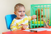 Little cute boy draws with crayons in the nursery — Stok fotoğraf