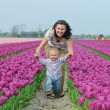 In Tulip Field. Mother with son in tulips field — 图库照片