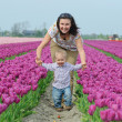 Stock Photo: In Tulip Field. Mother with son in tulips field