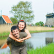 In Tulip Field. Happy young couple near Duch mills — Stock Photo