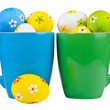 Easter eggs in cups on white background - Stockfoto