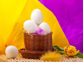 Eggs in straw basket with yellow and purple background — Stock Photo