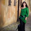Young woman wearing green with suitcase on street of old town — Stock Photo #5276664