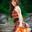 Young woman wearing orange dress in a park — Stock Photo #5277888