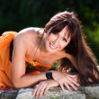 Young woman wearing orange dress in a park — Stockfoto
