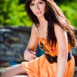 Young woman wearing orange dress in a park — Stockfoto #5278230