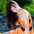 Stock Photo: Young woman wearing orange dress in a park