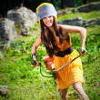 Young lawnmower woman working in a park — Stock Photo