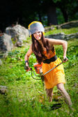 Jonge grasmaaier vrouw die werkt in een park — Stockfoto