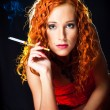 Sexy girl with red hair wearing red corset holding amber mouthpiece on blac — Stockfoto
