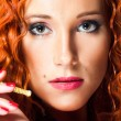 Royalty-Free Stock Photo: Close up portrait of sexy girl with red hair holding amber mouthpiece