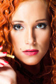 Close up portrait of sexy girl with red hair holding amber mouthpiece — Stock Photo