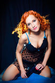 Sexy girl with red hair wearing short dress and blue ear rings on black — Stock Photo