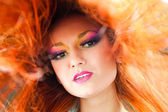 Beautiful girl with multicolored make-up and red long hair — Stock Photo