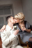 Happy bride and groom kissing in bedroom interior — Stock Photo