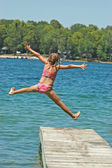 Young Girl Jumps Off Dock with Arms and Legs Spread — Стоковое фото