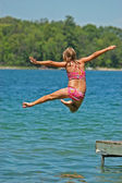 Young Girl Jumps Off Dock with Arms and One Leg Spread — Stock Photo