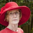 Beautiful mature woman outdoors in red hat — Stock Photo