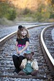 Little girl and teddy bear on railroad tracks — Stock Photo