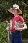 Beautiful mature woman with garden tools — Stock Photo