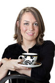 Beautiful brunette holding coffee cup and saucer — Stock Photo
