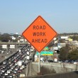 Road Work Ahead Sign with traffic - Stock Photo