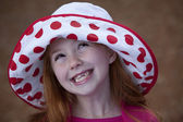 Cute little redhead in hat outdoors — Stock Photo