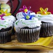 Cupcakes with sprinkles and plastic flowers — Stock Photo