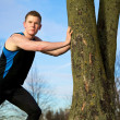 Young man streching against tree after workout — Stock Photo #5246196