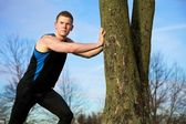 Young man streching against tree after workout — Stock Photo
