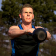 Young man doing kettlebell exercise outside in park — Stock Photo