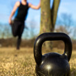 Closeup of Kettlebell with man in background — Stok fotoğraf