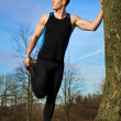 Young man stretching against tree after workout — Stock Photo #5270482