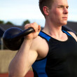 Young man doing kettlebell exercise outside — Stock Photo
