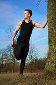 Young man stretching against tree after workout — Stock Photo