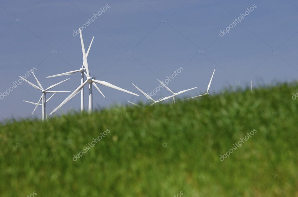 Group of windmills looming in a green meadow grass — Stock Photo #5344146